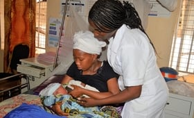 A midwife assists a mother with breast feeding her newborn baby at Princess Christian Maternity Hospital, Freetown